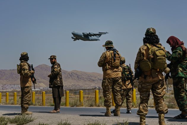 KABUL, AFGHANISTAN -- AUGUST 29, 2021: A C-17 Globemaster takes off as Taliban fighters secure the outer perimeter, alongside the American controlled side of of the Hamid Karzai International Airport in Kabul, Afghanistan, Sunday, Aug. 29, 2021. (MARCUS YAM / LOS ANGELES TIMES)