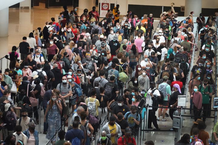 People stand in line to get through the TSA security checkpoint at Louis Armstrong New Orleans International Airport on Saturday in New Orleans, Louisiana.