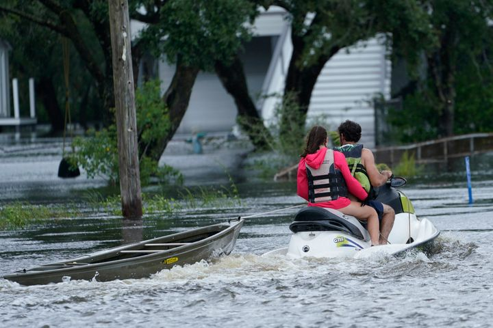 A local resident on a jet ski tows a canoe to a flooded house as outer bands of Hurricane Ida arrive on Sunday in Bay Saint Louis, Miss.