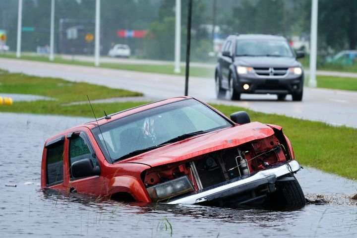 An abandoned vehicle is half submerged in a ditch next to a near flooded highway in Bay Saint Louis, Miss., on Sunday.