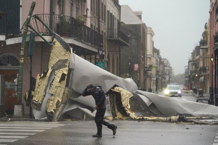 A man passes by a section of roof that was blown off of a building in the French Quarter by Hurricane Ida winds in New Orleans on Sunday.