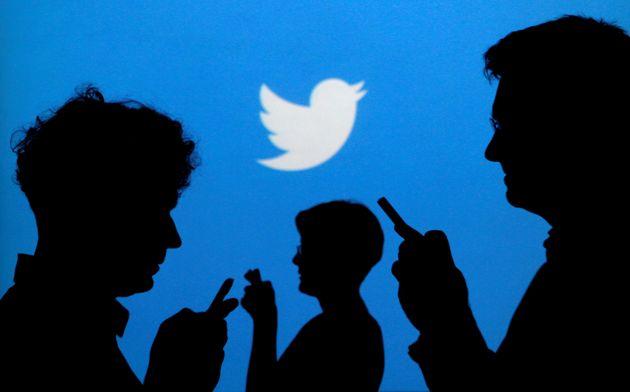 Varias personas usan sus móviles con el símbolo de Twitter de