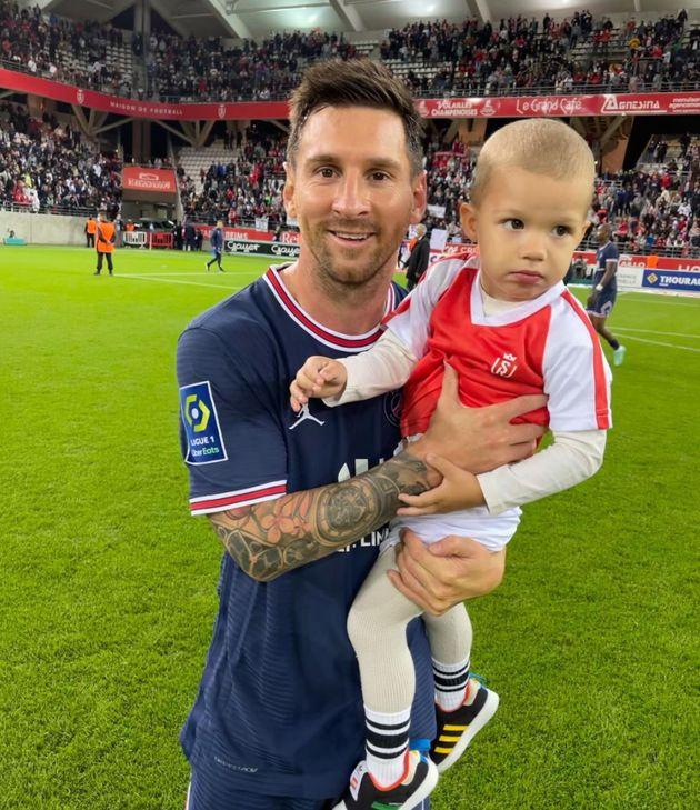 Lionel Messi pose avec le fils du gardien rémois Predrag Rajković le 29 août 2021 à...