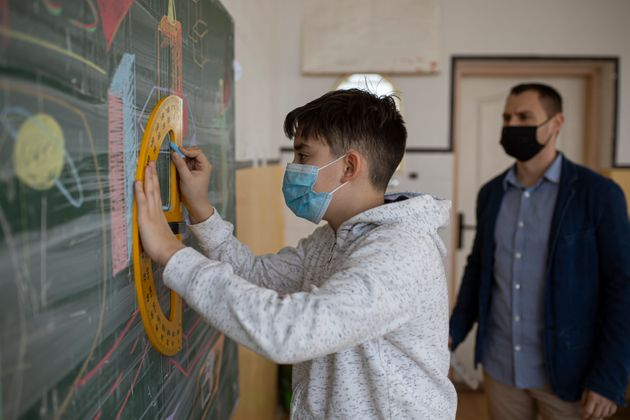 The teacher with the protective mask talks to the students about how to solve the mathematical equation