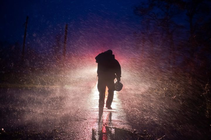 Montegut fire chief Toby Henry walks back to his fire truck in the rain as firefighters cut through trees on the road in Bourg, Louisiana as Hurricane Ida passes on August 29, 2021.