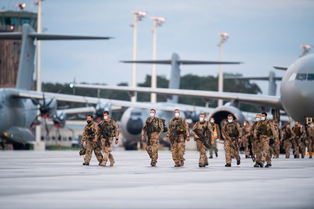 27 August 2021, Lower Saxony, Wunstorf: Soldiers disembark from the Bundeswehr's A400M transport aircraft and the Luftwaffe's Airbus A310 after landing at Wunstorf base in Lower Saxony. The first Bundeswehr soldiers have returned to Germany from their evacuation mission in Afghanistan. Three military planes landed at the Wunstorf airbase near Hanover shortly before 8:00 p.m. on Friday evening. An Airbus A310 of the German Air Force and two military transporters A400M were used for the return flight of the soldiers to Germany. The forces had taken off from Tashkent, the capital of Uzbekistan. The Bundeswehr had set up a hub there to fly Germans and threatened Afghans out of Kabul in short shuttle flights. Photo: Daniel Reinhardt/dpa (Photo by Daniel Reinhardt/picture alliance via Getty Images)
