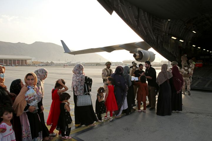 Afghans prepare to to be evacuated aboard a Qatari transport plane, at Hamid Karzai International Airport in Kabul, Afghanistan, August, 18, 2021.