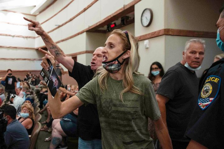 In this Aug. 12, 2021, file photo, protesters against a COVID-19 mandate gesture as they are escorted out of the Clark County