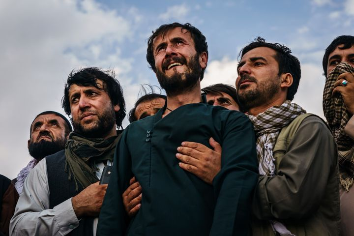 Ramal Ahmadi, center, is supported by family members as he weeps looking up at jet fighters circling above at the conclusion