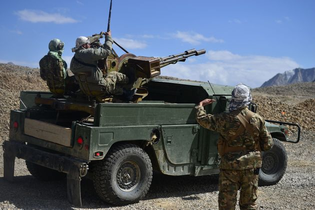 Afghan resistance movement and anti-Taliban uprising forces personnel patrol on an armoured humvee on...