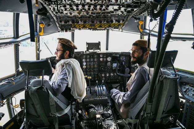 Taliban fighters sit in the cockpit of an Afghan Air Force aircraft at the airport in Kabul on August...