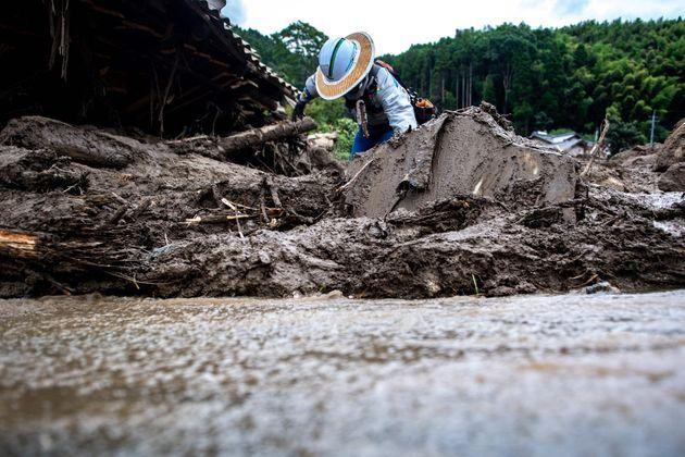 大雨による土砂崩れの現場で作業する建設会社の社員=2021年8月15日、佐賀県神埼市