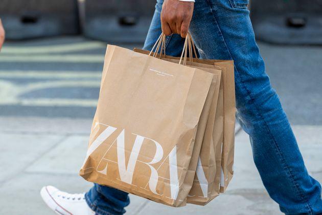 Un hombre lleva varias bolsas con ropa de