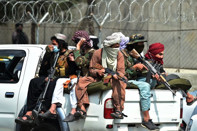 Taliban fighters guard outside the airport in Kabul on August 31,
