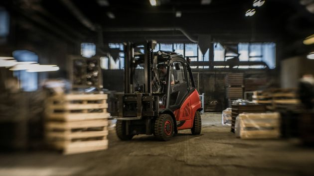 Red and black coloured forklift picking up wooden box with products inside production hall. Logistics, internal transport, engineering and people at work concept.