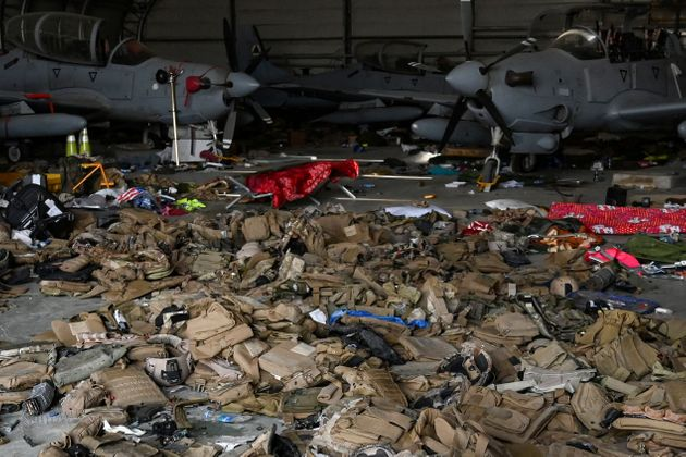 TOPSHOT - Afghan Air Force's A-29 attack aircrafts are pictured as armoured vests are lying on the ground inside a hangar at the airport in Kabul on August 31, 2021, after the US has pulled all its troops out of the country to end a brutal 20-year war -- one that started and ended with the hardline Islamist in power. (Photo by WAKIL KOHSAR / AFP) (Photo by WAKIL KOHSAR/AFP via Getty Images)