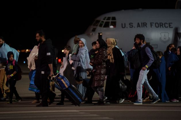 Afghan refugees, fleeing the Afghan capital Kabul, exit an US air force plane upon their arrival at Pristina International airport near Pristina on August 29, 2021. - Kosovo has offered to take in temporarily thousands of Afghan refugees evacuated by US forces from Kabul until their asylum claims are processed. (Photo by Armend NIMANI / AFP) (Photo by ARMEND NIMANI/AFP via Getty Images)