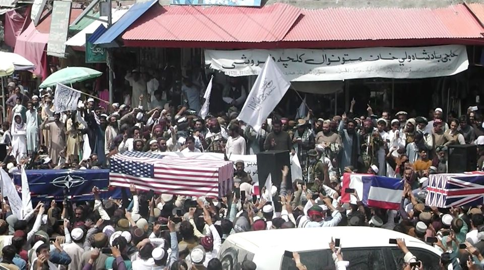 Crowd carries makeshift coffins draped in NATO's, US and a Union Jack flags during a mock funeral on...