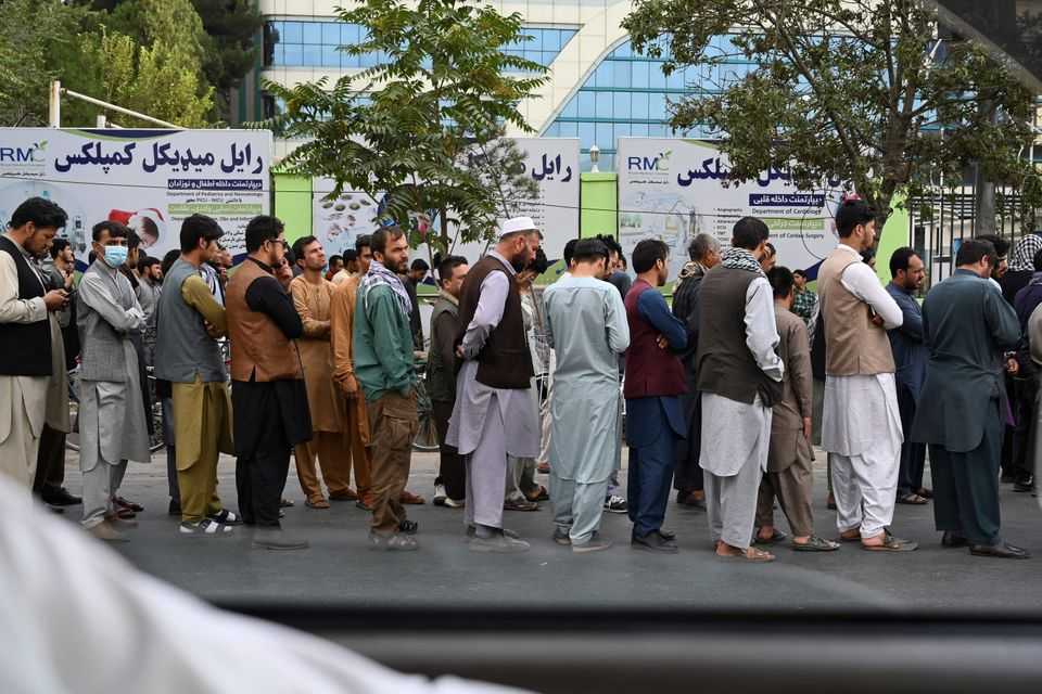 Afghans queue up as they wait for the banks to open and operate at a commercial area in