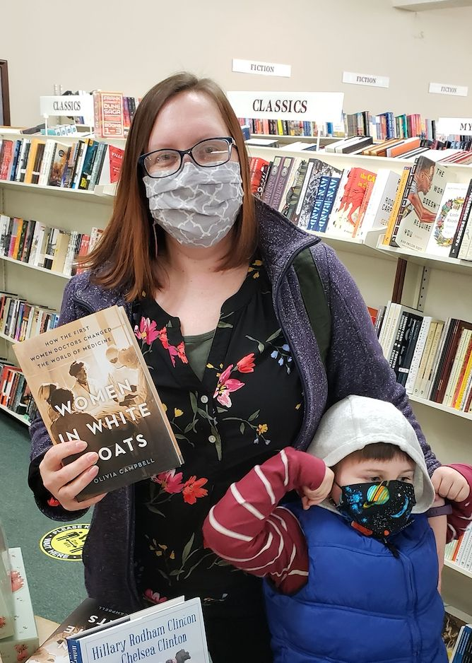 """The author with her son and her book, """"The Women in White Coats,"""" at a local independent bookstore, March 2021."""