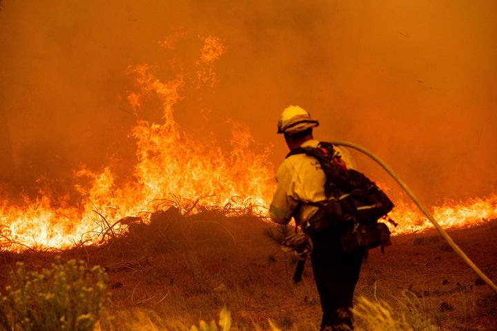 A firefighter battles the Caldor Fire along Highway 89, Tuesday, Aug. 31, 2021, near South Lake Tahoe, Calif.