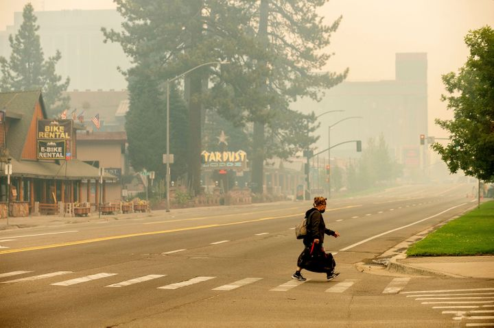 A woman crosses Highway 50 on Tuesday, Aug. 31, 2021, in South Lake Tahoe, Calif., which has been evacuated due to the Caldor Fire's approach.
