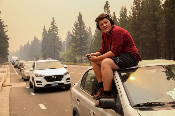 Victor Salas Jr.,15, sits on top of his car as he waits in evacuation traffic on Highway 50 out of South Lake Tahoe, Calif. on Monday, Aug. 30, 2021. Due to the threat of encroaching wildfire flames from the Caldor Fire, evacuation orders were issued Monday afternoon for all of South Lake Tahoe.