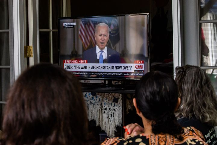 Military families and veterans watch President Joe Biden's speech announcing that all troops are out of Afghanistan on Aug. 3