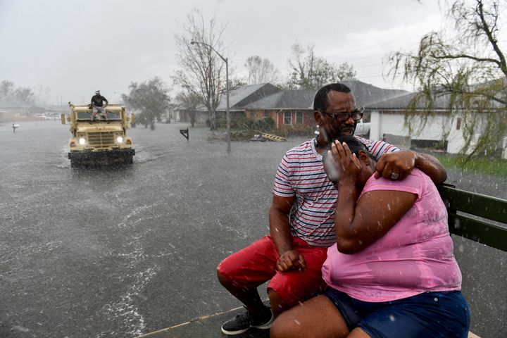 People react as a sudden rain shower soaks them with water while riding out of a flooded neighborhood in a volunteer high water truck assisting people evacuating from homes after neighborhoods flooded in LaPlace, Louisiana on August 30.
