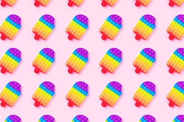 Pattern with rainbow pop it anti-stress toy isolated on pink background. Close-up.