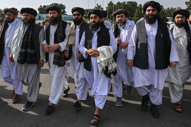 TOPSHOT - Taliban spokesman Zabihullah Mujahid (C, holding shawl) arrives as he is accompanied by officials to address a media conference at the airport in Kabul on August 31, 2021. - The Taliban joyously fired guns into the air and offered words of reconciliation on August 31, as they celebrated defeating the United States and returning to power after two decades of war that devastated Afghanistan. (Photo by WAKIL KOHSAR / AFP) (Photo by WAKIL KOHSAR/AFP via Getty Images)