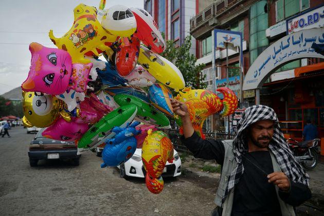 A balloon seller walks along a street in