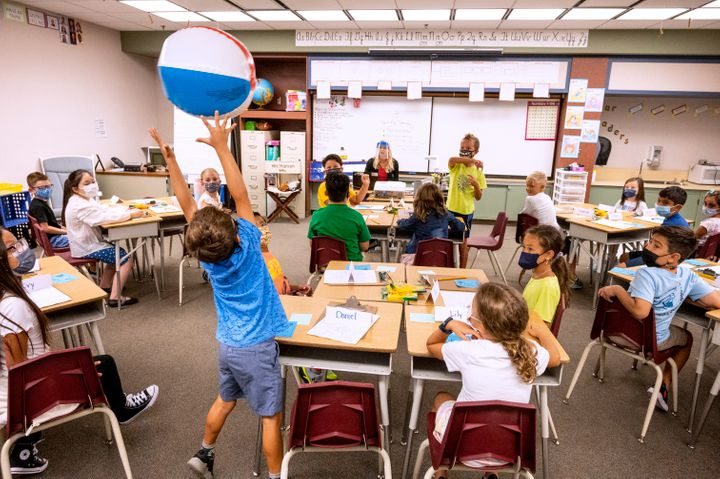 Students pass a beach ball to the next person on the list during roll call on the first day of class at Laguna Niguel Element
