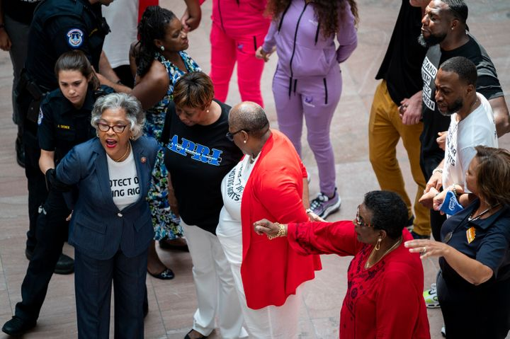 Chair of the Congressional Black Caucus Rep. Joyce Beatty (D-Ohio), left, is arrested by Capitol Police as 19 voting rights a