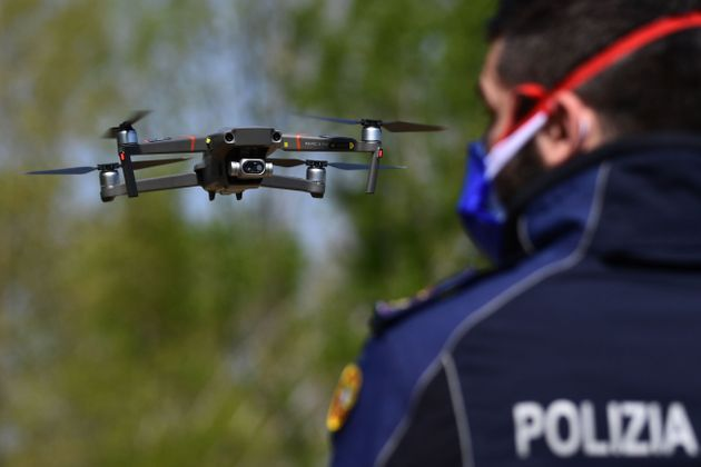 An officer of the municipal police pilots a DJI Mavic 2 Enterprise drone equipped with a thermal sensor for checking people's temperature on April 9, 2020 in Treviolo, near Bergamo, Lombardy, during the country's lockdown aimed at stopping the spread of the COVID-19 pandemic, caused by the novel coronavirus. (Photo by Miguel MEDINA / AFP) (Photo by MIGUEL MEDINA/AFP via Getty Images)
