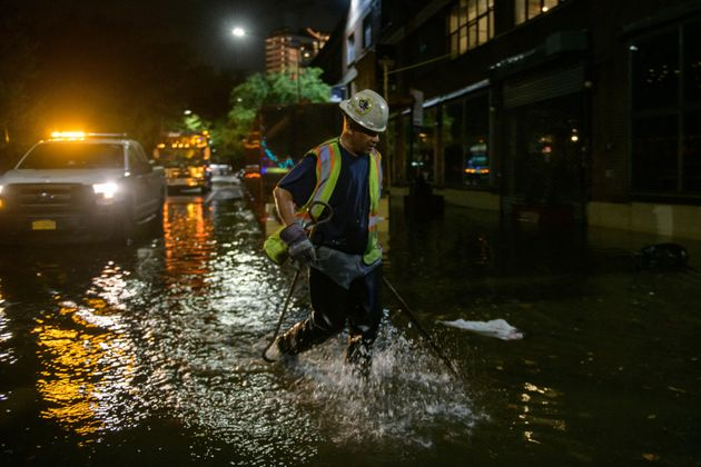 A worker unblocks drains on a street affected by floodwater in Brooklyn, New York early on September 2, 2021, as flash flooding and record-breaking rainfall brought by the remnants of Storm Ida swept through the area. (Photo by Ed JONES / AFP) (Photo by ED JONES/AFP via Getty Images)