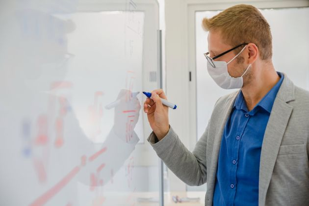 School teacher man wearing protective face mask writing on white blackboard while teaching mathematic in a high school classroom in COVID-19 outbreak at reopen schools after coronavirus quarantine and lockdown