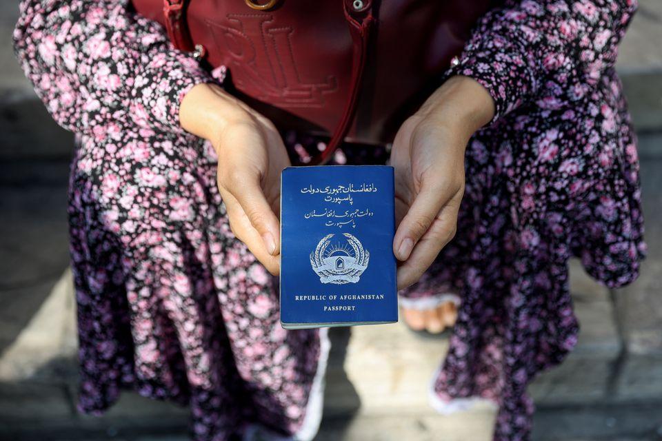 Una mujer afgana sostiene su pasaporte ante la embajada de Alemania en Teherán, en busca de