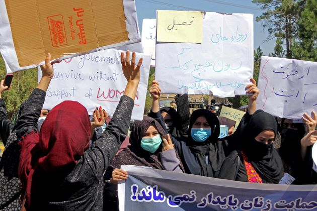 Afghan women hold placards as they take part in a protest in Herat on September 2, 2021. - Defiant Afghan...