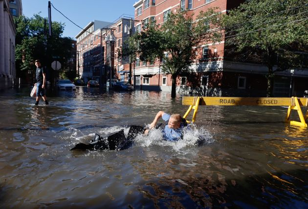 HOBOKEN, NJ - SEPTEMBER 2: A man falls off his bike into a flooded street the morning after the remnants of Hurricane Ida drenched the New York City and New Jersey area on September 2, 2021 in Hoboken, New Jersey. (Photo by Gary Hershorn/Getty Images)