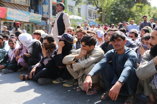 Afghans line up outside a bank to take out cash after Taliban's