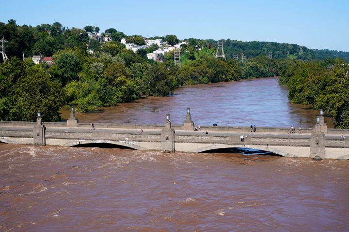The Schuylkill River exceeds its bank in the Manayunk section of Philadelphia on Thursday in the aftermath of downpours and h