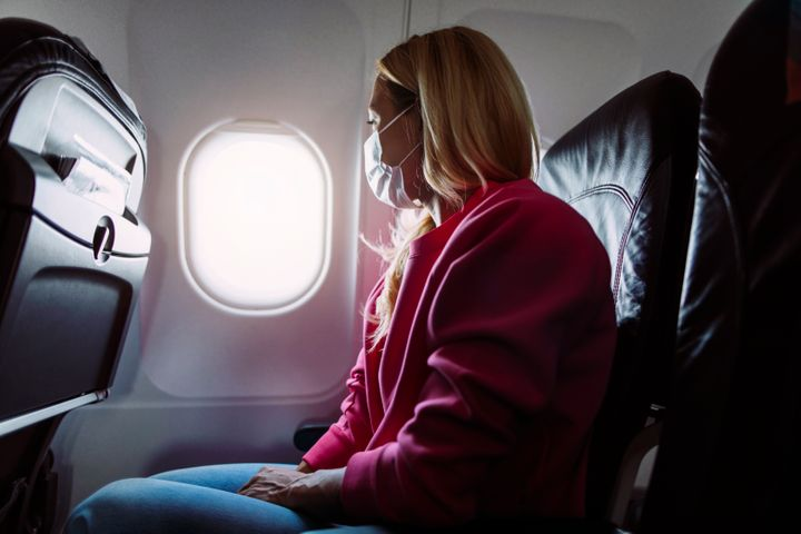 Side shot of a young blond woman sitting in an airplane and looking out of the window