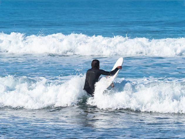 Un surfero, en una playa