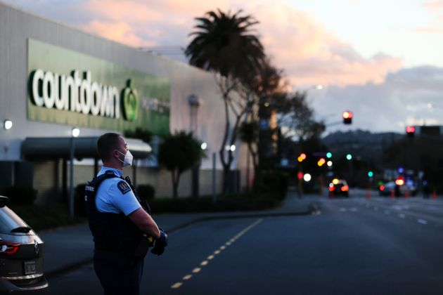 Police standing outside the supermarket where the stabbings occurred on
