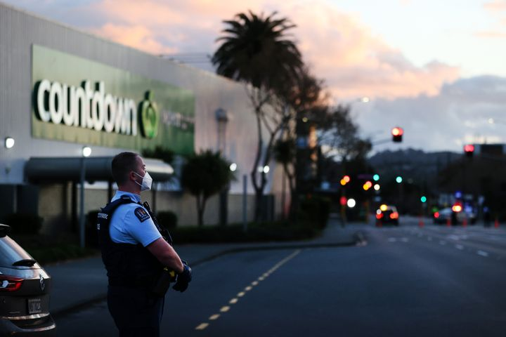 Police standing outside the supermarket where the stabbings occurred on Friday.