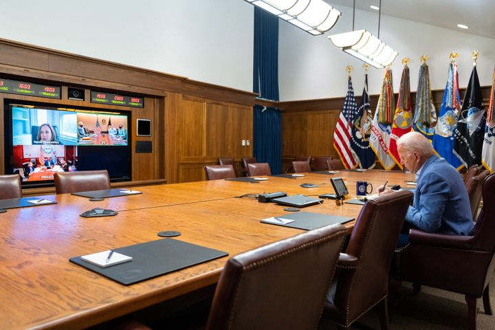 In this White House handout, President Joe Biden and Vice President Kamala Harris (on screen) speak with their national security team about efforts to draw down the civilian footprint in Afghanistan on Aug. 16, 2021.