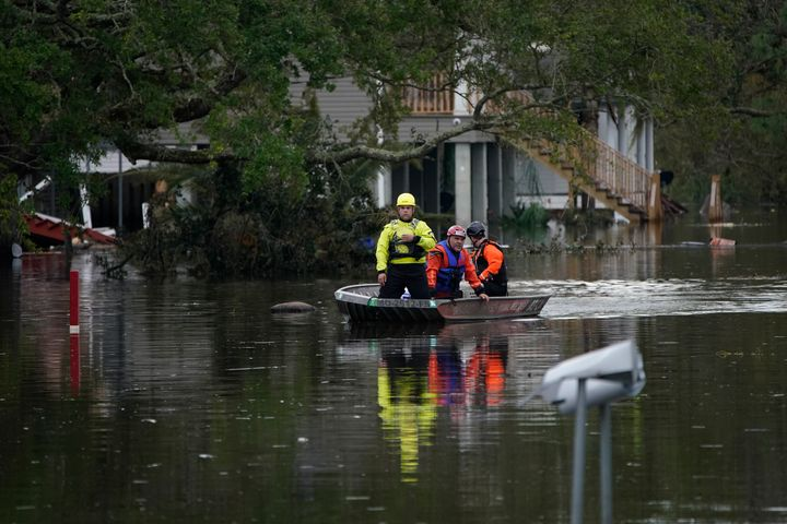 People conducting an animal rescue operation drive a boat down a flooded street in the aftermath of Hurricane Ida, Wednesday,