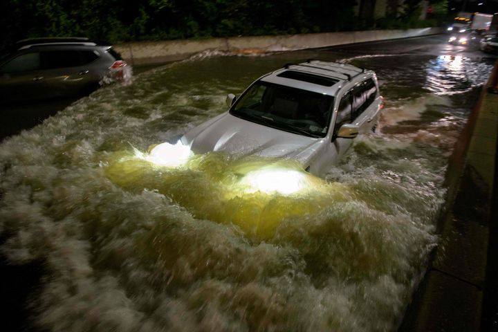 A motorist drives a car through a flooded expressway in Brooklyn, New York early on September 2, 2021.