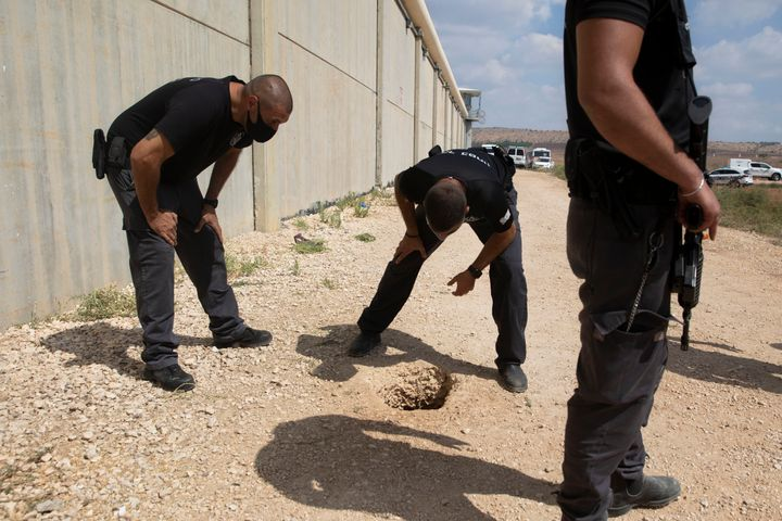Police officers and prison guards inspect the scene of a prison escape outside the Gilboa prison in northern Israel, Monday,